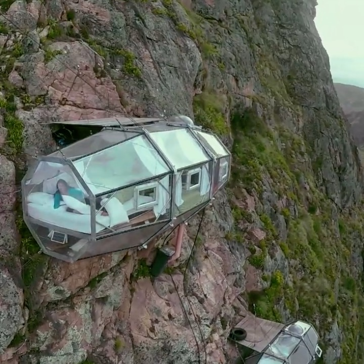 This glass hotel room hangs from a cliff